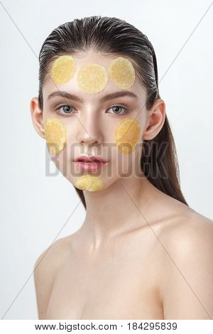 Beautiful young cheerful woman with refreshing mask on her face isolated on white background