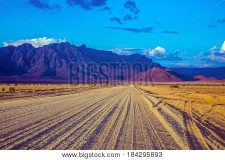 The dirt road in Namib-Naukluft national park goes to distant mountains. Travel to Namibia. Ecotourism in Africa