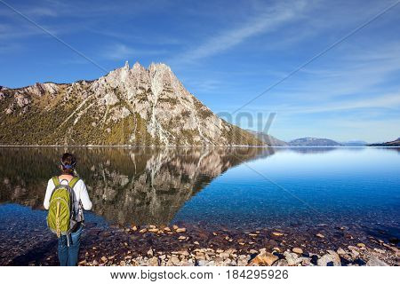 The elderly woman with green tourist backpack admires lake and mountain in Bariloche. The concept of exotic and extreme tourism. Picturesque summer in Argentina