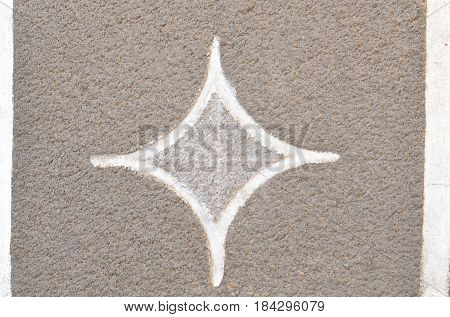 Abstract counter-relief in the form of a four-pointed star on the wall.