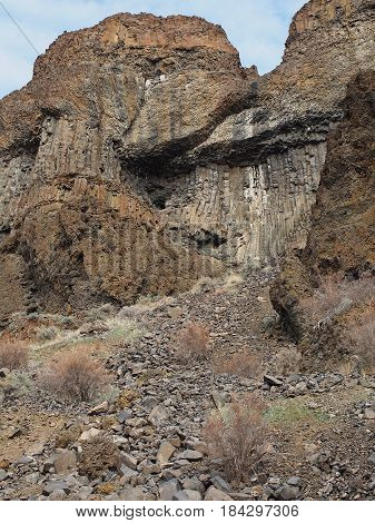 Layers of jagged and porous boulders and rocks detailing a cliff on a rugged hillside with bushes and wild grasses on a spring day in Central Oregon.