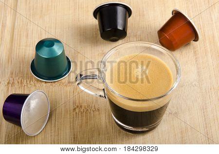 A glass of espresso with nespresso capsules around