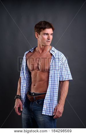 The stylish cowboy is showing his abs.