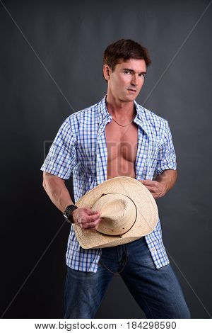 The majestic cowboy is holding his cap.