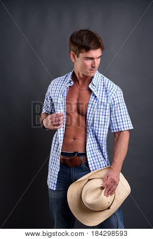 The wild cowboy is holding his hat.