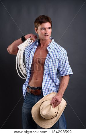 The cute cowboy is holding his hat.
