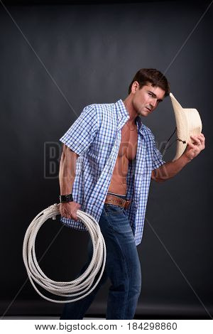 The sexy cowboy is holding his hat.