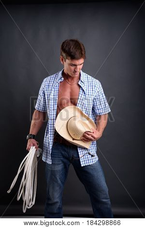 The hunky man is holding a cowboy hat.