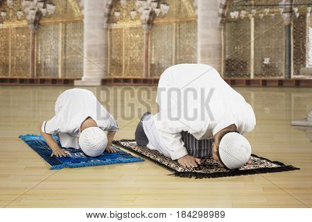 Picture of Asian family wearing Islamic clothes while posing prostration in the mosque