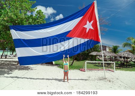 Cayo Coco island, Playo Coco beach, Cuba, Aug.10, 2015, amazing gorgeous view of a little girl on tropical beach stretching her arms to Cuban flag on sunny beautiful day