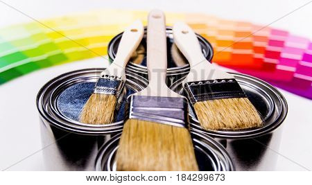 Painting brushes, paint cans, paint samples, paint concept, paint inside cans with paint color samples in background, yellow paint, white paint, red peint, three cans of different paint, paint samples from pink paint to dark blue paint
