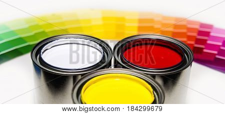 painting cans, painting samples, painting concept, painting inside cans with painting color samples in background, yellow painting, white paint, red painting, three cans of different painting, painting samples from pink painting to dark blue painting,