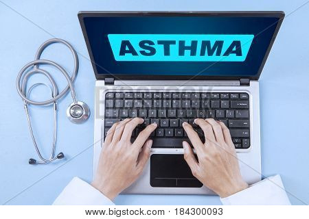 Top view of Asian doctor's hands typing on the laptop with asthma word on the screen