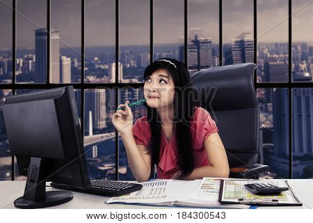 Picture of female entrepreneur is daydreaming and working with a computer while sitting near the window