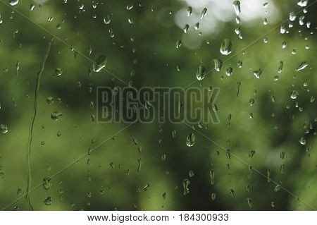 Rainy summer day raindrops on wet window glass horizontal bright abstract rain water background pattern detail macro closeup detailed green blue dark vivid gray waterdrops gentle bokeh pluvial rainfall season concept