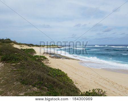 Waves break and crash towards the Hanakailio Beach with cloudy skyline on the North Shore of Oahu Hawaii.