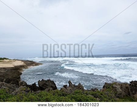 Waves break and crash towards the Kaneakua Cove with dramatic lava rock outcropping on the North Shore of Oahu Hawaii.