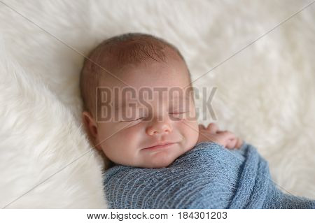 Sleeping nine day old newborn baby boy with a smile on his face he is