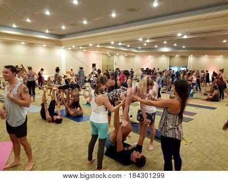 NORTH SHORE HAWAII - FEBRUARY 25: People balance each other during indoors at Acroyoga jam at Wanderlust yoga event on the North Shore Hawaii on February 25 2017.
