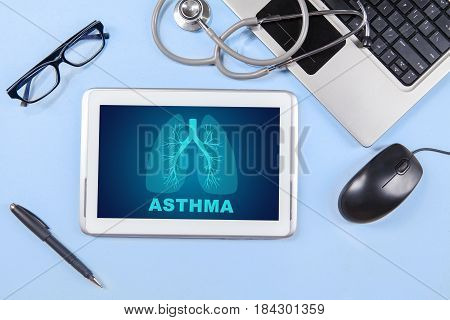 Closeup of lungs symbol and asthma word on the digital tablet with work equipment on the table