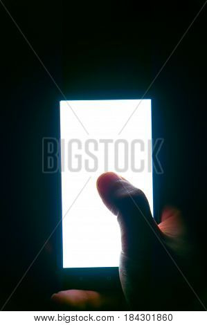vertical white screen of the phone in hand and finger play game dark background