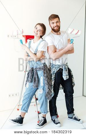 Young happy couple holding rolls while making repairs in new home