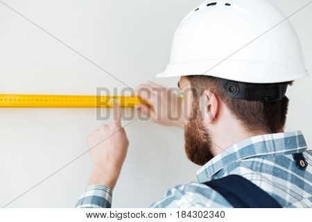 Back view of man builder in helmet using ruler to measure length isolated