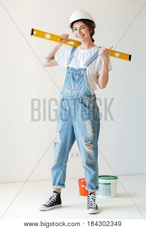 Full-length image of smiling woman with measuring tape looking camera isolated