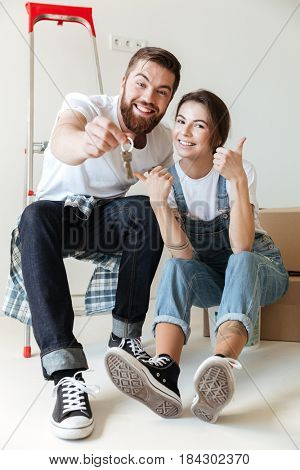 Young happy couple showing keys from new home sittng on boxes
