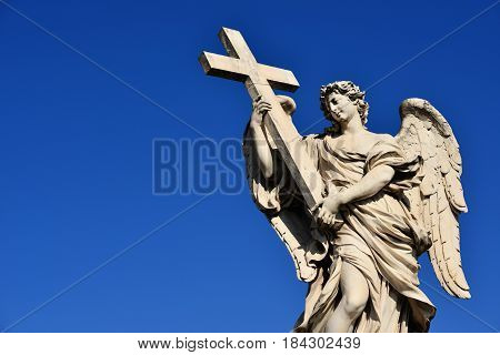 Angel holding Holy Cross statue a 17th century baroque masterpiece in Rome (with copy space)