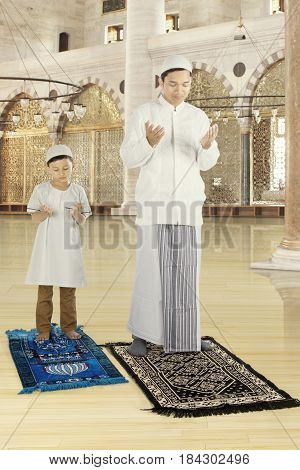 Portrait of muslim father praying in the mosque with his son while wearing islamic clothes