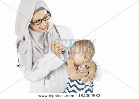 Portrait of Muslim pediatrician checking temperature her patient with a digital thermometer in the studio