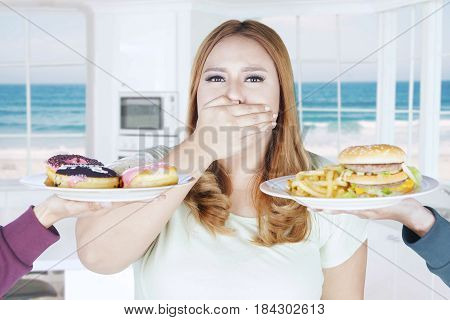Portrait of obese woman refusing unhealthy food while closed her mouth with hand