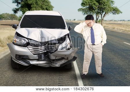 Image of overweight businessman looks stress with a broken car in the roadside