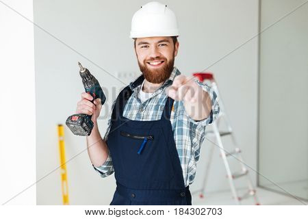 Young hardworking man with drill pointing at camera isolated
