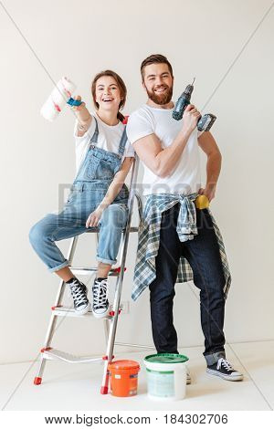 Happy young couple showing tools for repair while standing near ladder isolated