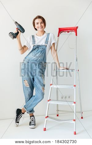 Smiling woman with drill leaning on ladder isolated over white