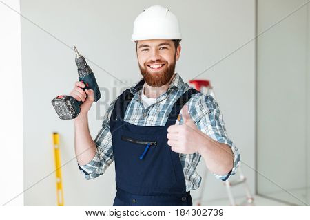 Portrait of cheerful bearded man builder with drill showing thumb up isolated