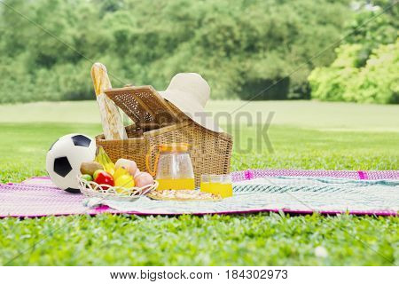 Picture of a picnic basket on mat with foods drink straw hat and a soccer ball. Shot at green meadow