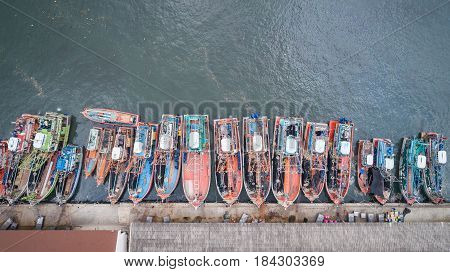 Row of fishing boats standing at the sea in Phuket Thailand. Aerial view from flying drone