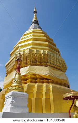 Large gold Temple Stupa outline by a clear blue sky.
