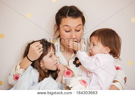 Little daughter feed mother while she hugging children