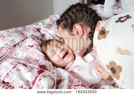 Pretty young mother kissing her laughing daughter on bed