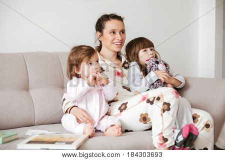 Cheerful family, mom and daughters, hugging and sitting on couch and looking up