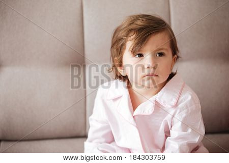 Upset child sitting on sofa and looking away