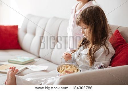 Cute little girl eating popcorn from dish at home