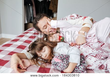Young mother hugging her cute smiling daughters while they lying in bed at home