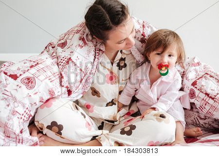 Young woman mother sitting in bed in blanket with her cute daughter