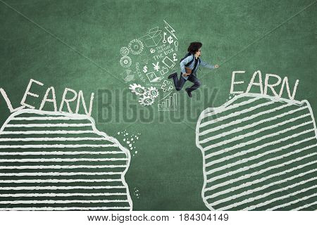 Young student jumping between gap with learn and earn words while holding a book