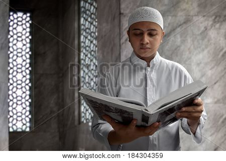 Religious muslim man reading koran in mosque